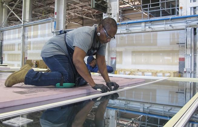 Woman working on prefabrication of glass panels for Northwestern Mutual